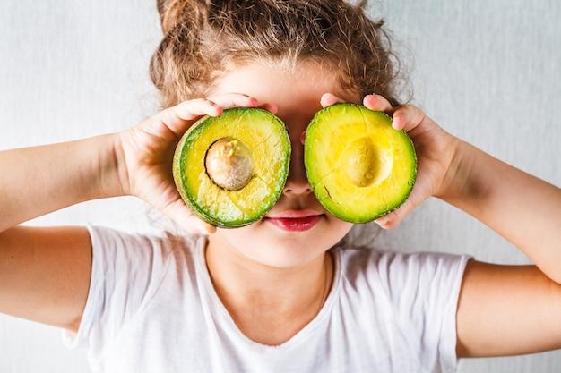 Gesundes babynahrungskonzept, mädchenkind hält geschnittene avocado anstelle der augen, Premium Fotos