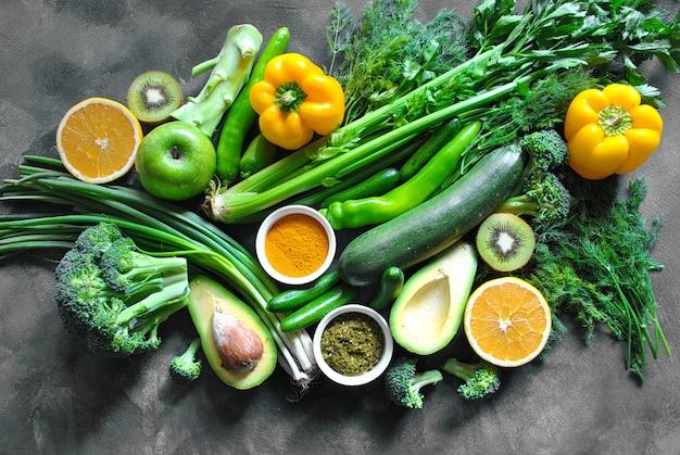 Gesundes essen hintergrund. konzept von gesunden lebensmitteln, frischem gemüse, gewürzen und früchten. auf einem dunklen hölzernen hintergrund. kopierraum Premium Fotos