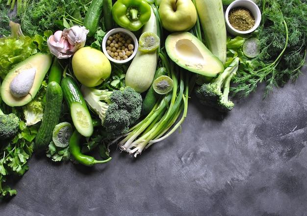 Gesundes essen hintergrund. konzept von gesunden lebensmitteln, frischem gemüse und obst. auf grauem hölzernem hintergrund. draufsicht. speicherplatz kopieren. Premium Fotos