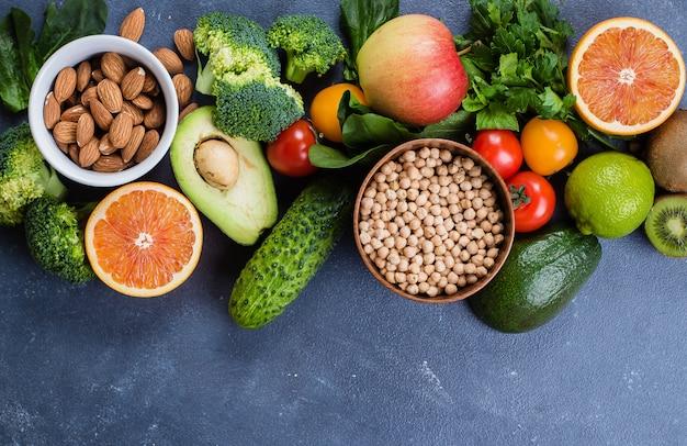 Gesundes essen sauber. rohe früchte, gemüse, nüsse, getreide auf konkretem steintabellenhintergrund Premium Fotos