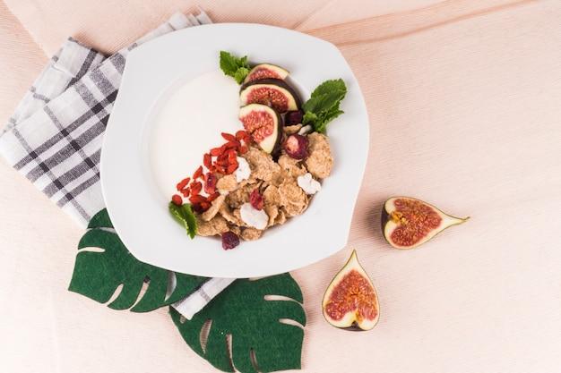 Gesundes frühstück auf teller mit gefälschten monstera-blättern; feigenscheiben und küchenserviette Kostenlose Fotos