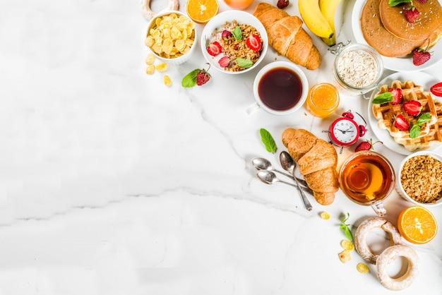Gesundes frühstück, das konzept, verschiedenes morgenlebensmittel - pfannkuchen, waffeln, hörnchenhafermehlsandwich und granola mit joghurt, frucht, beeren, kaffee, tee, orangensaft, weißer hintergrund isst Premium Fotos