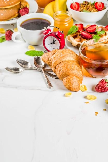 Gesundes frühstück, das konzept, verschiedenes morgenlebensmittel - pfannkuchen, waffeln, hörnchenhafermehlsandwich und granola mit jogurt, frucht, beeren, kaffee, tee, orangensaft isst Premium Fotos