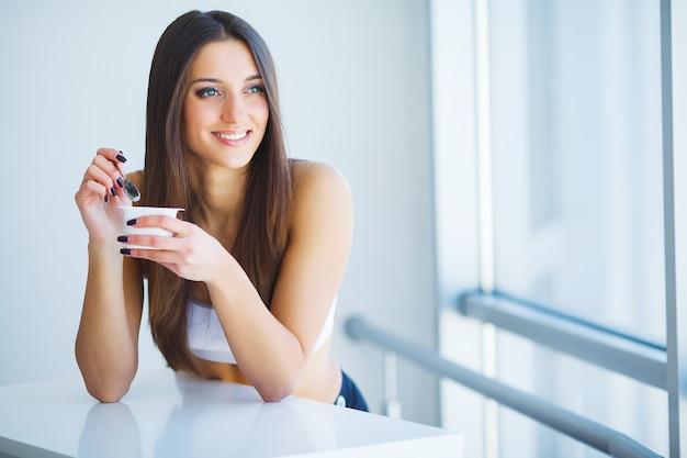 Gesundes frühstück. frau mit glas joghurt, beeren und hafer Premium Fotos