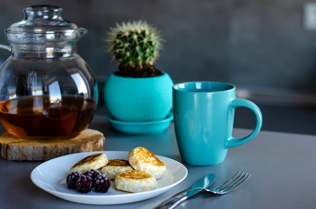 Gesundes frühstück gemacht von den pfannkuchen vom hüttenkäse mit beeren und grünem tee in einer glasteekanne. Premium Fotos