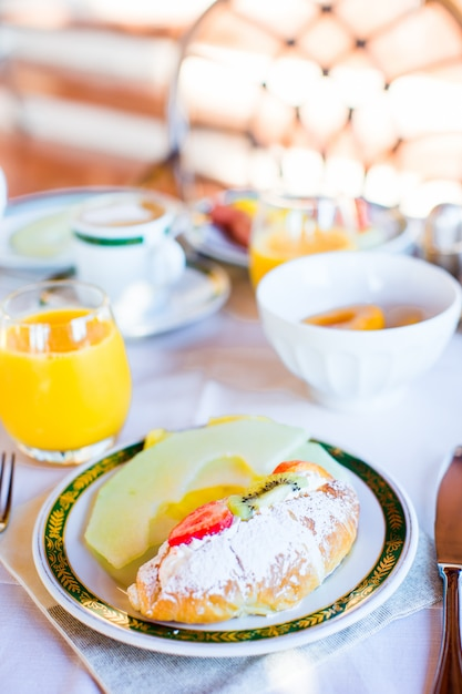 Gesundes frühstück mit frischem saft und süßem hörnchen im restauranterholungsort im freien Premium Fotos