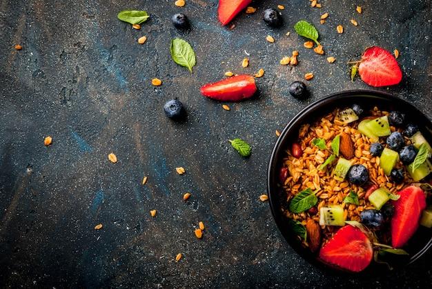 Gesundes frühstück mit müsli oder müsli mit nüssen und frischen beeren und früchten Premium Fotos