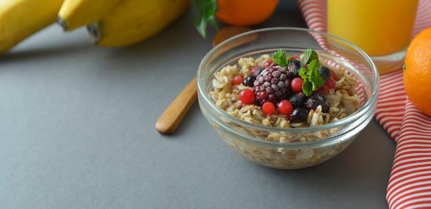 Gesundes frühstück, schüssel mit haferflocken, gefrorene beeren. haferbrei mit früchten. banner. Premium Fotos
