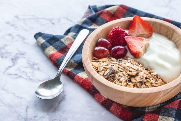 Gesundes frühstück. schüssel selbst gemachtes muesli mit jogurt und frischen früchten auf marmortabelle. Premium Fotos