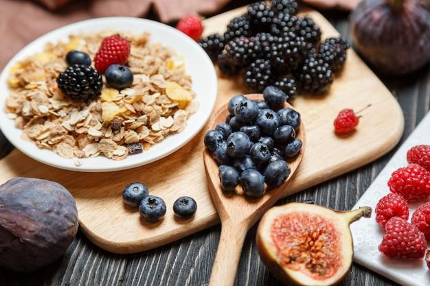 Gesundes frühstücksset, müsli und beeren auf dunklem rustikalem Premium Fotos