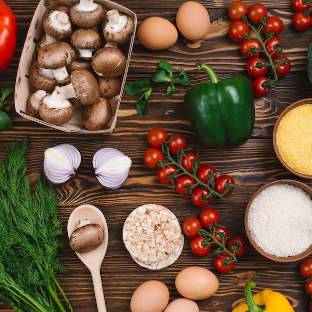 Gesundes gemüse; eier; puffreiskuchen und polenta auf schreibtisch aus holz Kostenlose Fotos
