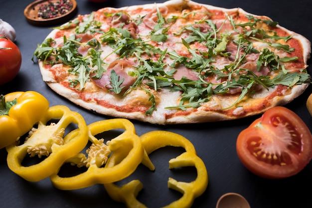 Gesundes gemüse und arugulapizza über küche worktop Kostenlose Fotos
