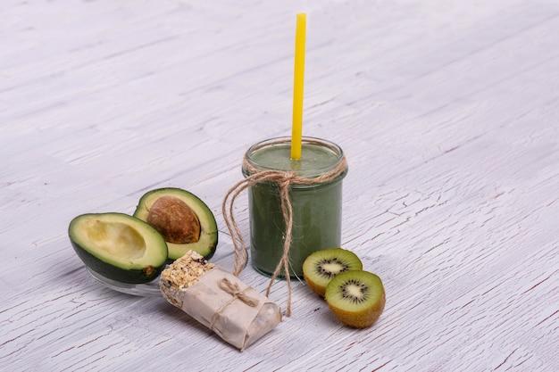Gesundes grünes smoothie mit avocado und kiwi liegen auf dem tisch Kostenlose Fotos