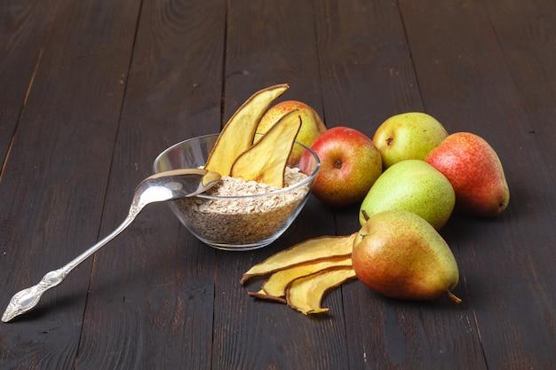 Gesundes hausgemachtes bio-müsli oder müsli mit hafer, getrockneten feigen, rosinen, bananenchips und gerösteten mandeln und haselnüssen in einem glas zum frühstück oder snack Premium Fotos