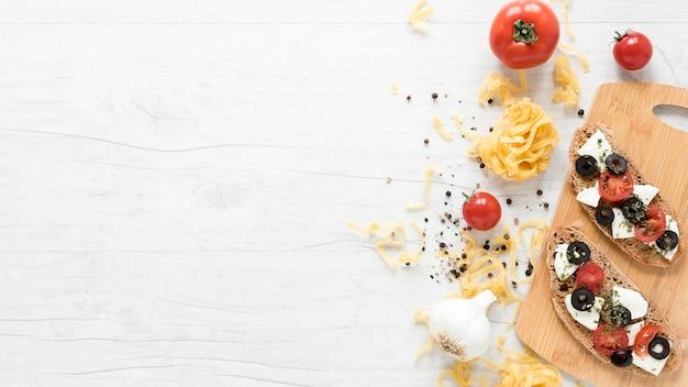 Gesundes italienisches brotsandwich auf schneidebrett mit gewürzen; tomaten-tagliatelle-nudeln Kostenlose Fotos