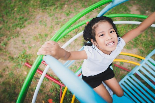 Gesundes kleinkind spielt im hinterhof, glücklich mit dem schwingen, den schaukelpferden, den diawagen. Premium Fotos