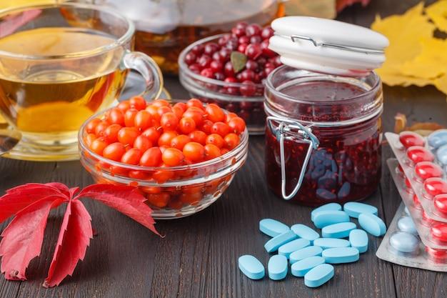 Gesundes konzept. winterbeerentee mit preiselbeeren, honig und thymian in einer glasschale auf holztisch. alternativ zur traditionellen medizin Premium Fotos