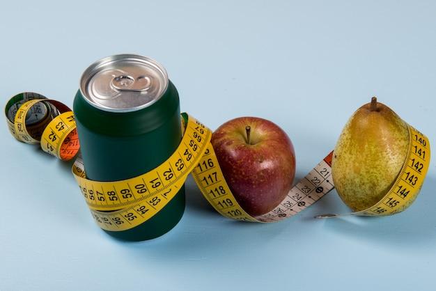 Gesundes leben kontrastiert mit dose soda und obst mit einem maßband Premium Fotos