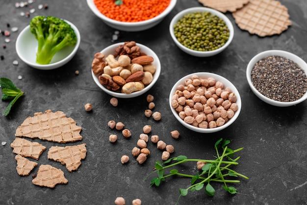 Gesundes lebensmittel des strengen vegetariers auf einem konkreten hintergrund mit kopienraum. nüsse, bohnen, gemüse und samen Premium Fotos
