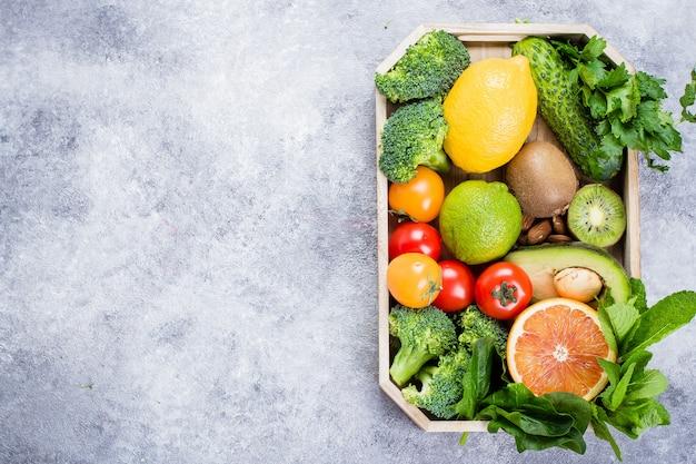 Gesundes lebensmittel sauberes konzept. obst, gemüse, nüsse, getreide in holzschale Premium Fotos
