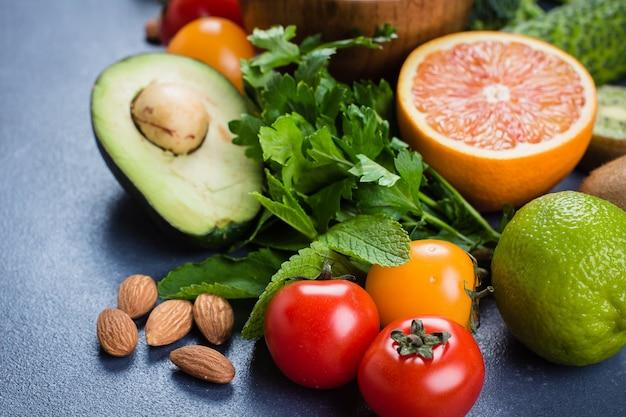 Gesundes lebensmittel sauberes konzept. rohe früchte, gemüse, nüsse, getreide auf konkretem steintabellenhintergrund Premium Fotos