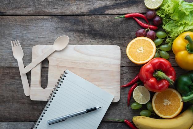 Gesundes lebensmittelkonzept des frischen organischen gemüses und des hölzernen schreibtischhintergrundes. Premium Fotos