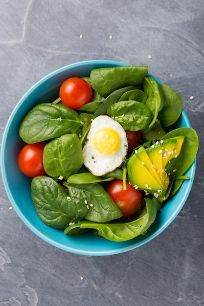 Gesundes lebensmittelkonzept. salat in der blauen schüssel auf dunklem hintergrund. Premium Fotos