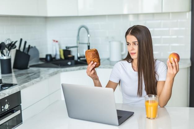 Gesundes lebensmittelkonzept. schwere entscheidung. ihre sportliche frau wählt zwischen gesundem essen und süßigkeiten, während sie auf leichter küche steht. Kostenlose Fotos