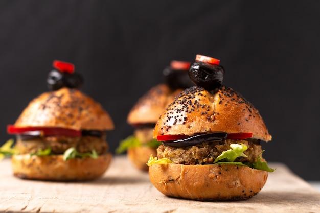 Gesundes lebensmittelkonzept selbst gemachte minihamburger auf hölzernem brett Premium Fotos