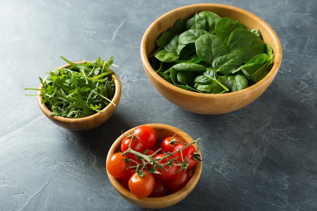 Gesundes lebensmittelkonzept. zutaten für salat. spinat in schüssel, rucola, tomaten. Premium Fotos