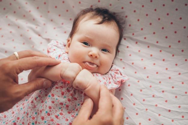 Gesundes lebensstilkonzept, ivf-neugeborenes baby ballte seine fäuste vor ihm und zeigt seine zunge Premium Fotos