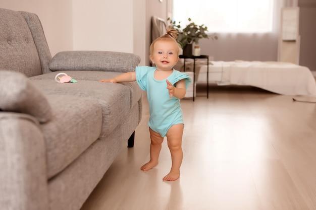 Gesundes mädchen in einem raum neben einem grauen sofa lernt laufen Premium Fotos