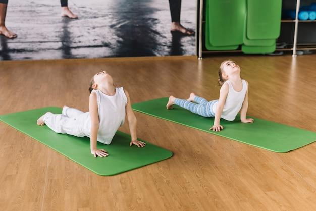 Gesundes mädchen zwei, das auf grüner matte über hölzernem schreibtisch trainiert Kostenlose Fotos