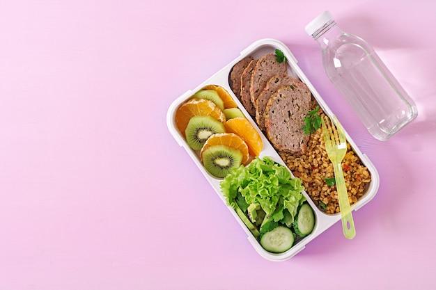 Gesundes mittagessen mit bulgur, fleisch und frischem gemüse und obst auf einer rosa oberfläche. eignung und gesundes lebensstilkonzept. brotdose. ansicht von oben Kostenlose Fotos