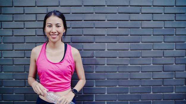 Gesundes schönes junges asiatisches läuferfrau trinkwasser weil gefühl müde nach dem laufen auf der straße Kostenlose Fotos