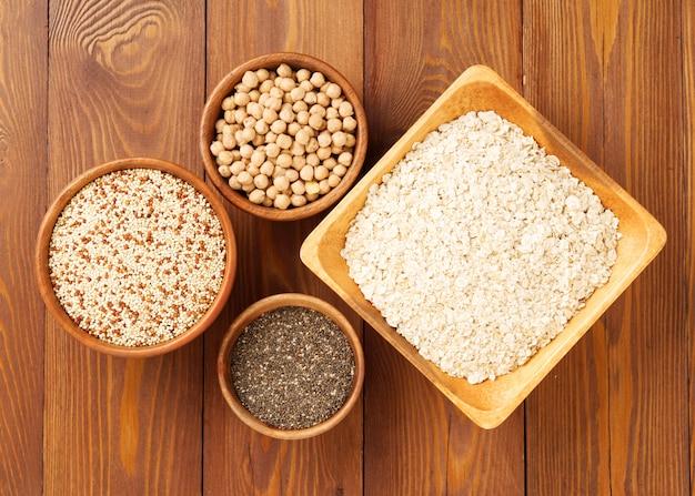 Gesundes superlebensmittel - trockene kichererbsen, quinoa, chia auf braunem hölzernem hintergrund, draufsicht Premium Fotos