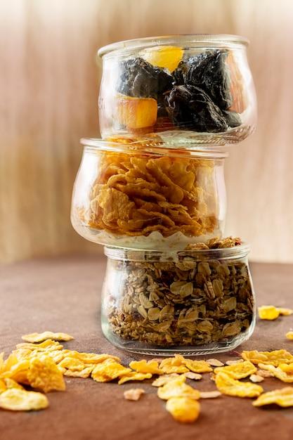 Gesundes und leckeres frühstücksgranola, cornflakes und trockenfrüchte in gläsern. vegetarier und veganer. hochkant. copyspace. Premium Fotos