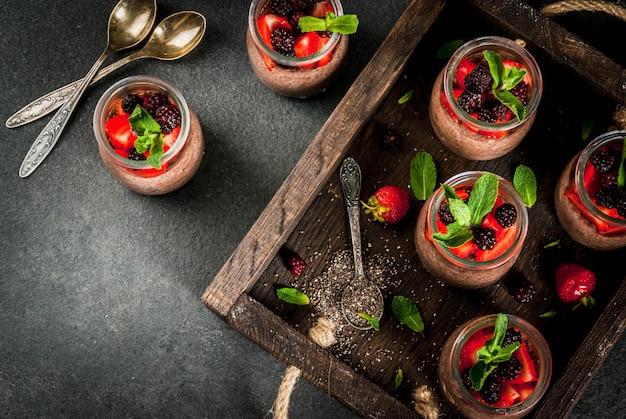 Gesundes veganes frühstück. dessert. alternatives essen. pudding mit chiasamen, frischen erdbeeren, brombeeren und minze. in einem alten holztablett. ansicht von oben Premium Fotos