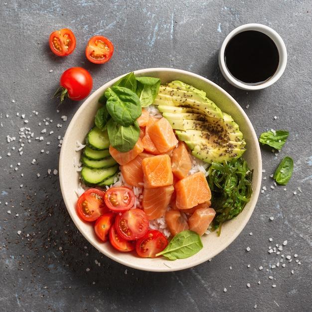 Gesundes veganes lebensmittelkonzept sackschale mit lachs, avocado, gemüse und chiasamen Premium Fotos
