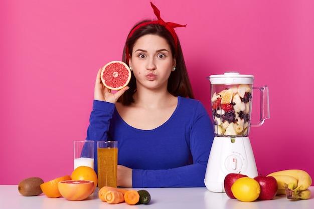 Gesundes vegetarisches mädchen öffnet ihre augen weit, bläst ihren mund, schaut direkt in die kamera und hält obst in einer hand. verschiedene früchte stehen auf dem tisch und im mixer und kochen köstlichen smoothie. Kostenlose Fotos
