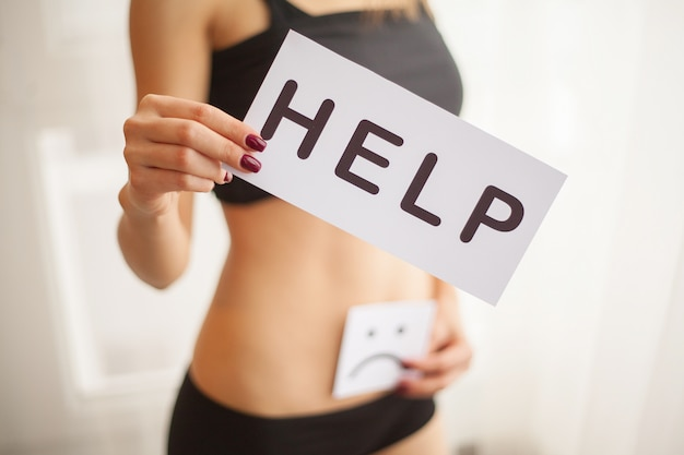 Gesundheit der frau. weiblicher körper, der symbol-hilfekarte nahe magen hält Premium Fotos