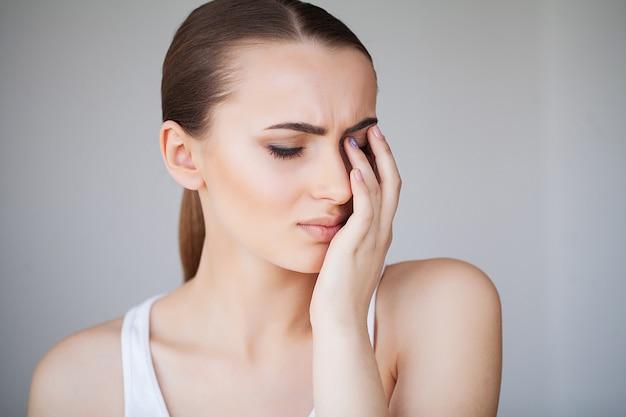 Gesundheit und kopfschmerzen. schöne frau, die die starken kopfschmerzen, schmerz fühlend hat Premium Fotos