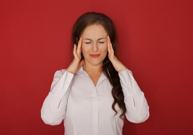 Gesundheit und schmerz. gestresste erschöpfte junge frau, die starken spannungskopfschmerz hat. Premium Fotos