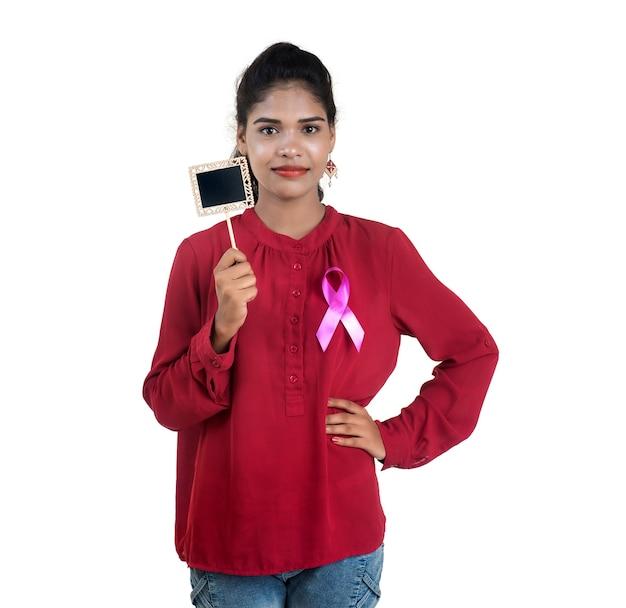 Gesundheits- und medizinkonzept - junge frauenhände, die rosa brustkrebs-bewusstseinsband und kleine tafel halten Premium Fotos