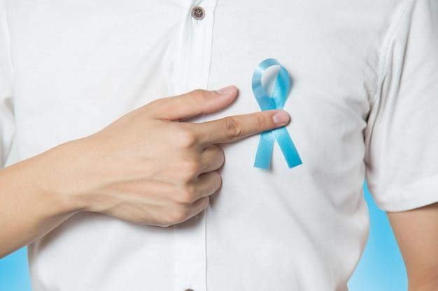 Gesundheitskonzept der männer - nah oben von der männlichen hand, die auf hellblaues band für prostat zeigt Premium Fotos
