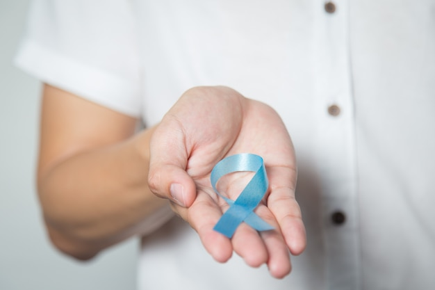 Gesundheitskonzept der männer - nah oben von der männlichen hand, die hellblaues band für prostatakrebs hält. Premium Fotos
