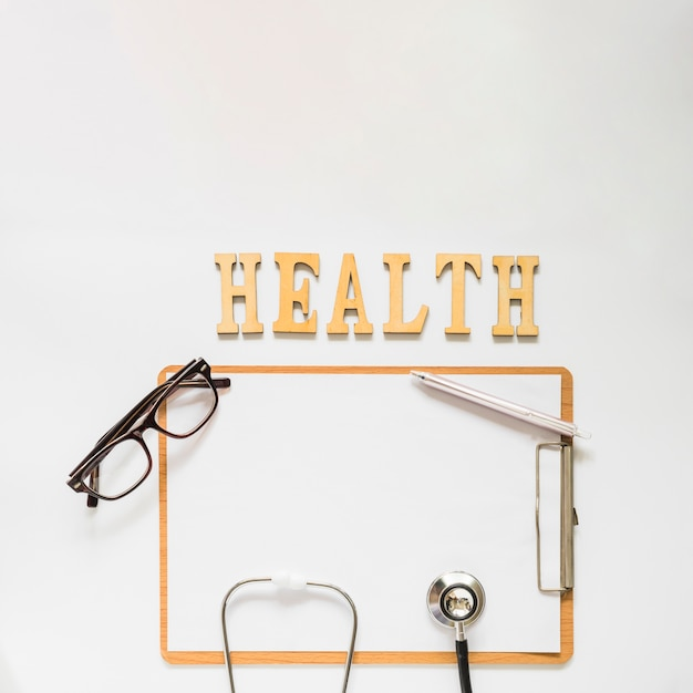 Gesundheitstext nahe dem klemmbrett mit brillen; stethoskop und stift auf weißem hintergrund Kostenlose Fotos