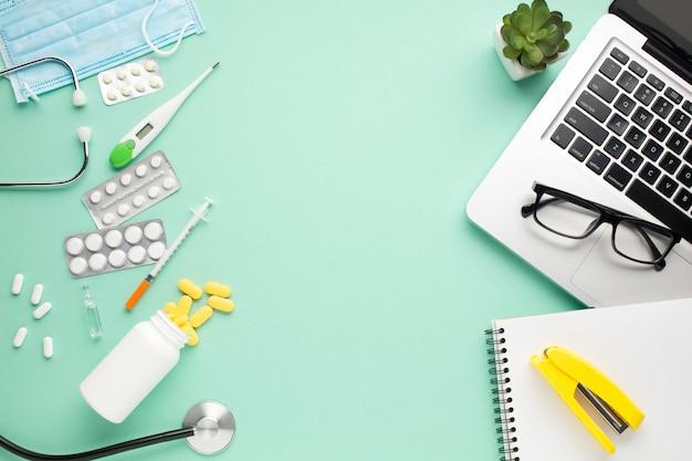 Gesundheitswesenausrüstung und bürozubehöre mit saftiger anlage auf grünem hintergrund Kostenlose Fotos