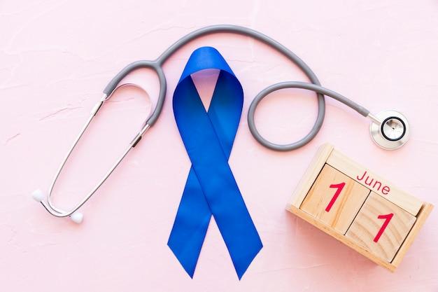 Gesundheitswoche der männer mit blauem band und stethoskop mit hölzernem kalender Kostenlose Fotos
