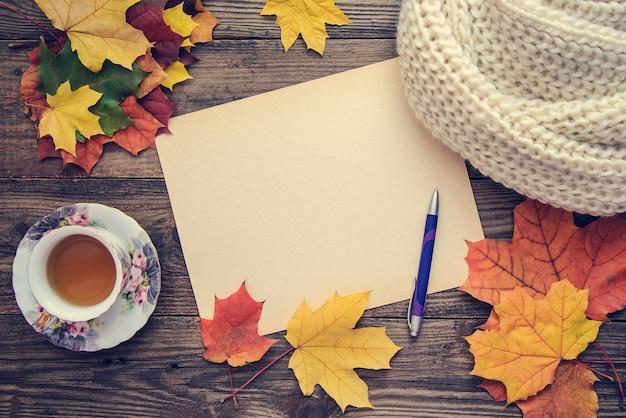 Getontes bild mit herbstlaub, einer tasse tee und einem notizbuch Premium Fotos